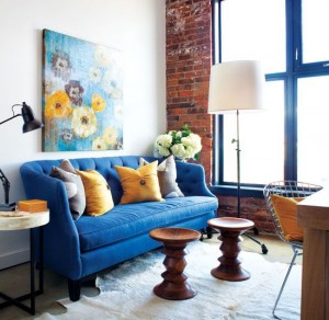 White provides the neutral backdrop to this bright blue sofa and beautifully complementary mustard yellow accents